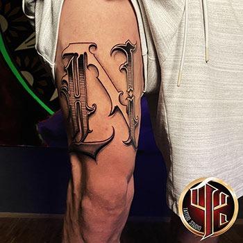 Buchstabe-N-Tätowierung-am-Oberschenkel-tattoo-studio-pattos-ke